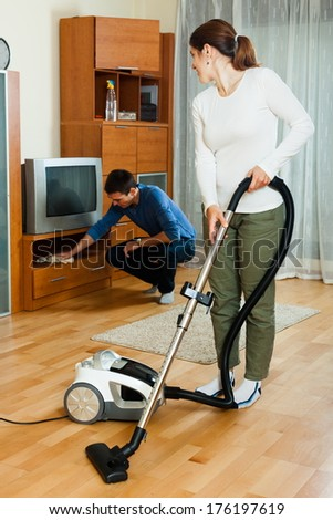 Adult couple doing housework together in home - stock photo