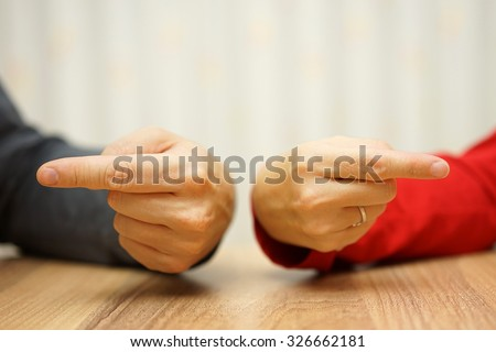 adult couple has difficulties in relationship an both shows the finger at himself and herself - stock photo