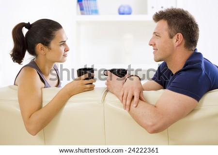 Adult couple sitting on sofa at home drinking coffe, talking, smiling.