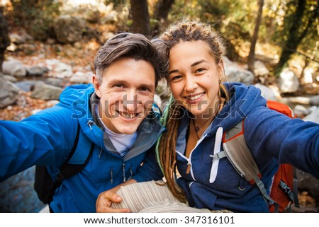 Adult couple with backpacks hiking in the beautiful forest and making selfie - stock photo