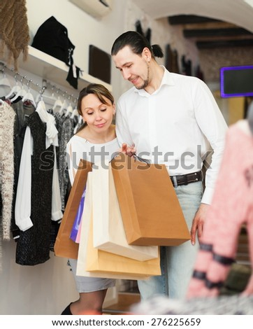 Adult couple with shopping bags at boutique
