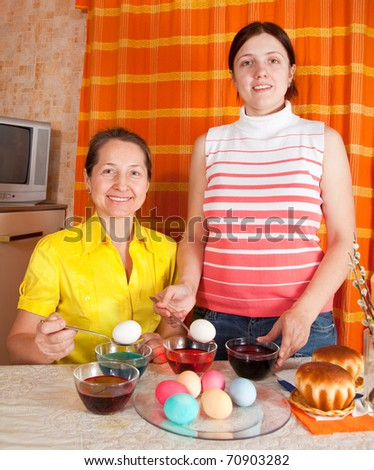 Adult daughter and mother  coloring eggs for Easter holiday - stock photo
