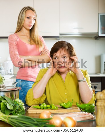 Adult daughter and mother having conflict  in home kitchen - stock photo