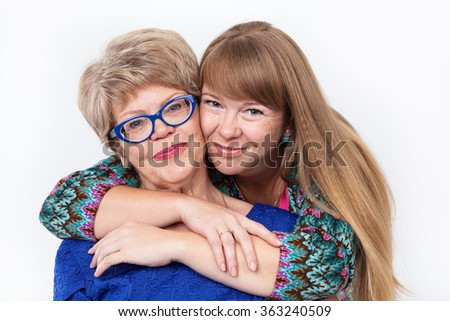 Adult daughter embracing her senior mother, smiling faces looking at camera, on white background - stock photo