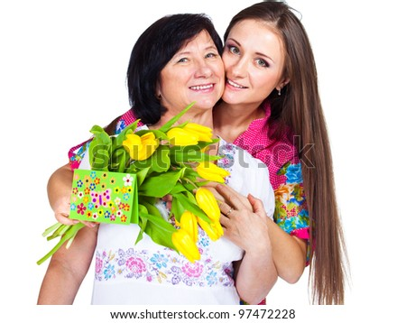 Adult daughter greeting mom with card and flowers