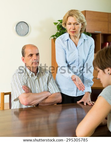 Adult daughter having serious talking with elderly parents at home