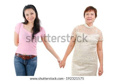 Adult daughter holding hands with mother isolated on white background. Mixed race Asian family portrait.  - stock photo