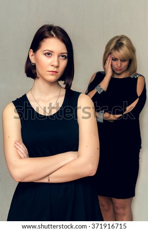 Adult daughter quarrel with her mother. Conflict of generations. Selective focus on the foreground. - stock photo