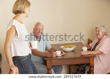 Adult Daughter Sharing Cup Of Tea With Senior Parents In Kitchen - stock photo