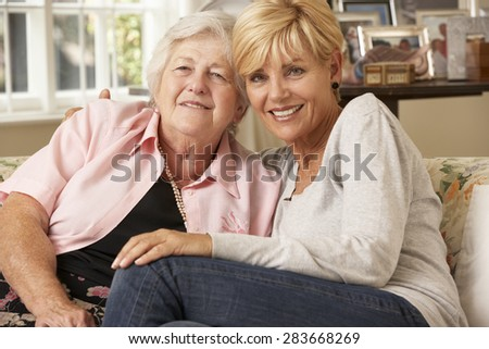 Adult Daughter Visiting Senior Mother Sitting On Sofa At Home - stock photo