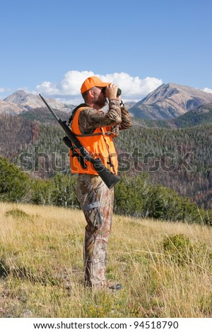 adult deer hunter looking through binoculars - stock photo