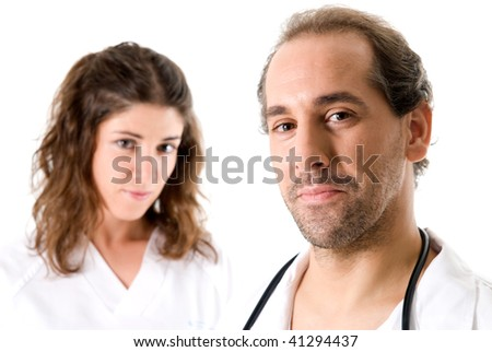 Adult doctor and young nurse on white background. Focused on doctor. - stock photo