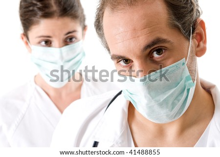 Adult doctor and young nurse with mask on white background, focused on doctor. - stock photo