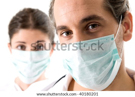Adult doctor and young nurse with mask on white backgrund, focused on doctor. - stock photo
