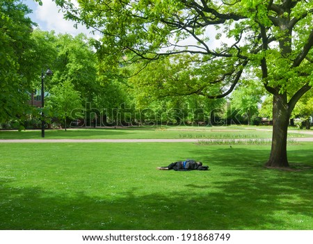 Adult drunk man sleeping down on the ground in the park - stock photo