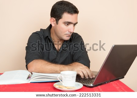 Adult education - Hispanic man studying or doing office work at home - stock photo