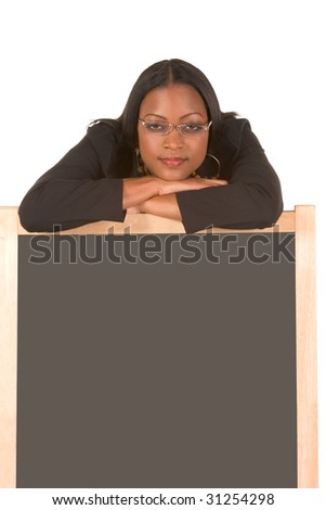 Adult education series. Young attractive ethnic woman in business suit and skewed eyeglasses with her head leaning on blackboard - stock photo