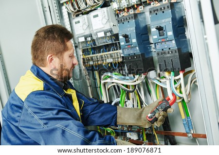 adult electrician builder engineer in front of his co-worker screwing equipment in fuseboard - stock photo