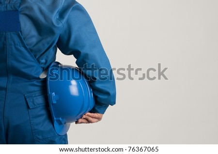 adult engineer holding a blue helmet - stock photo