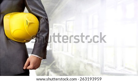 adult engineer or inspector hand holding yellow plastic helmet for workers security over big empty space room with window in perspective and door background No face Copy space for inscription - stock photo