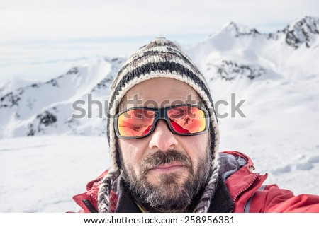 Adult european man with beard, sunglasses and hat, taking selfie on snowy slope with the beautiful snowcapped italian Alps in the background. Natural colors. - stock photo