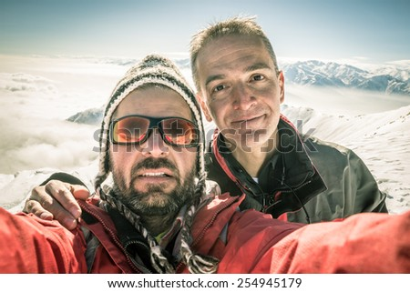 Adult european men taking selfie on the mountain summit with snowcapped italian Alps in background. Concept of friendship and sharing achievments. Backlight, toned image, old retro touch, desaturated. - stock photo