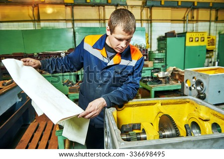Adult experienced industrial worker assembling the reduction gear box on production line manufacturing workshop - stock photo