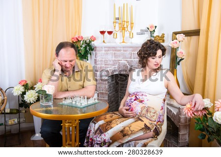 adult family in anticipation of the child, family evenings, a pregnant woman after 40 years. parents, male and female, husband and wife - stock photo