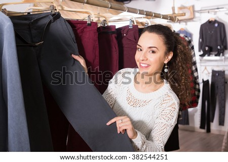 Adult female brunette choosing new trousers and smiling