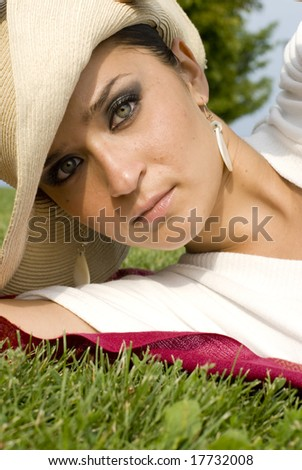 Adult female laying in the grass wearing a cream hat on a sunny day - stock photo