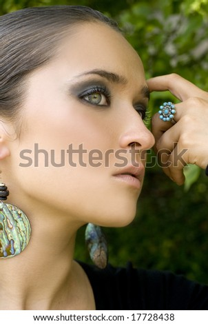 Adult female posing with turquoise jewelry on a bright day - stock photo