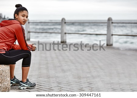 Adult female runner sitting down to catch her breath after her fitness orientated lifestyle morning run along the ocean side on the promenade - stock photo