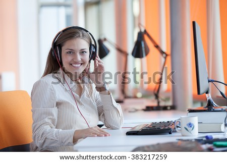 Adult female secretary with headphones doing customer service in a callcenter