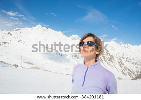 Adult female skier with backpack and sunglasses watching the sun in the ski resort of La Thuile, Aosta Valley. Italian french Alps. Concepts of spending free time on famous mountain areas. - stock photo