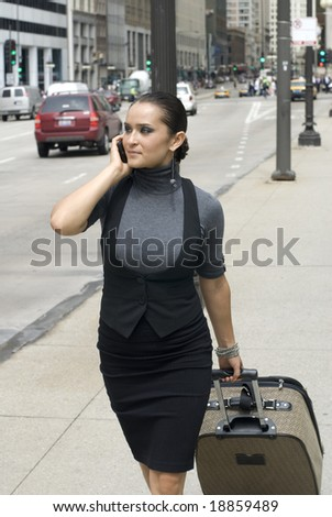 Adult female walking down the street pulling a suitcase while on a cell phone - stock photo