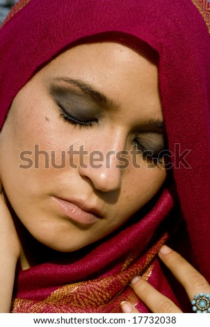 Adult female with fuchsia head scarf with her eyes closed on a bright day - stock photo