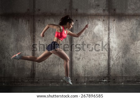adult fit girl running on dark background - stock photo