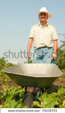 Adult gardener Holding  agricultural equipment in summer time - stock photo