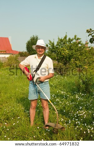 Adult gardener is fixing lawn trimmer  in garden - stock photo