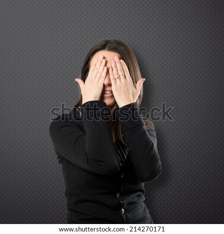 Adult girl crossing his fingers over black background