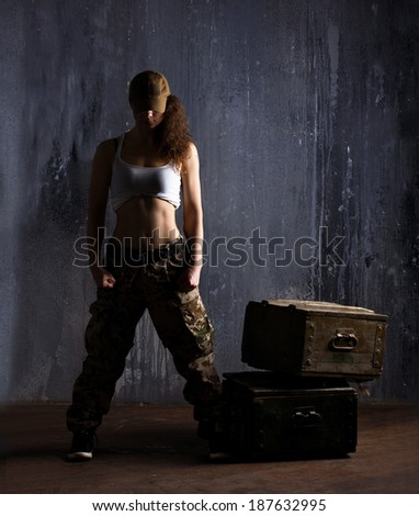 adult girl in khaki clothes standing near military boxes on dark grunge wall background - stock photo