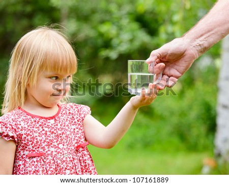 Adult giving mug of water to little girl outdoors - stock photo