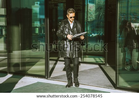 adult glamour man walks out of doors with newspaper in hands outdoors - stock photo