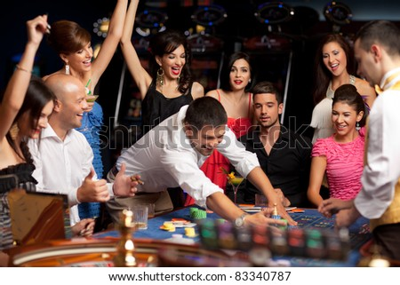 adult group celebrating friend winning at roulette - stock photo