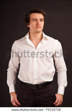 Adult guy in the white shirt on a black background