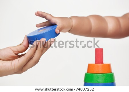 Adult hand gives a building block and baby learns to grip it - stock photo