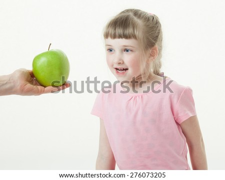 Adult hand giving a green apple for pretty little girl, white background - stock photo