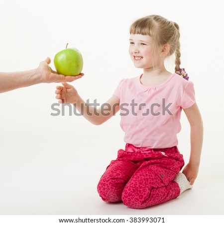 Adult hand giving a green apple for pretty little girl, white background
