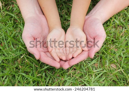 Adult hands holding kid hands  - stock photo