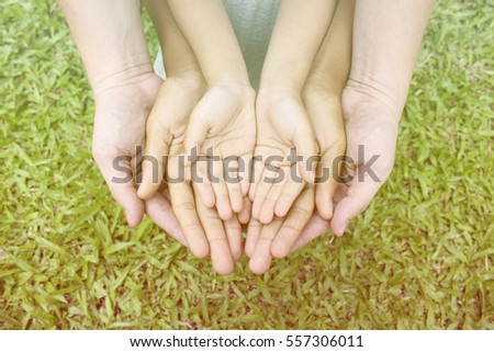 Adult hands holding kid hands (hand, help, hope) over green grass